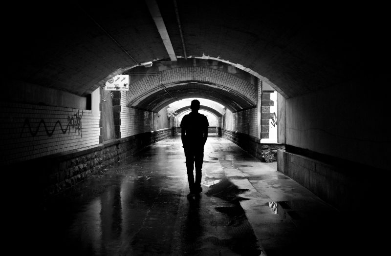 black and white photo of a man walking in a tunnel